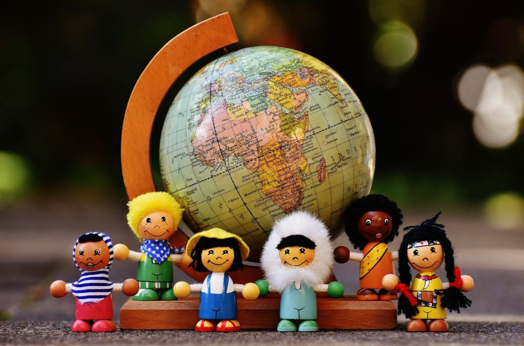Small globe with dolls from around the world demonstrating Facebook ads can reach anywhere.