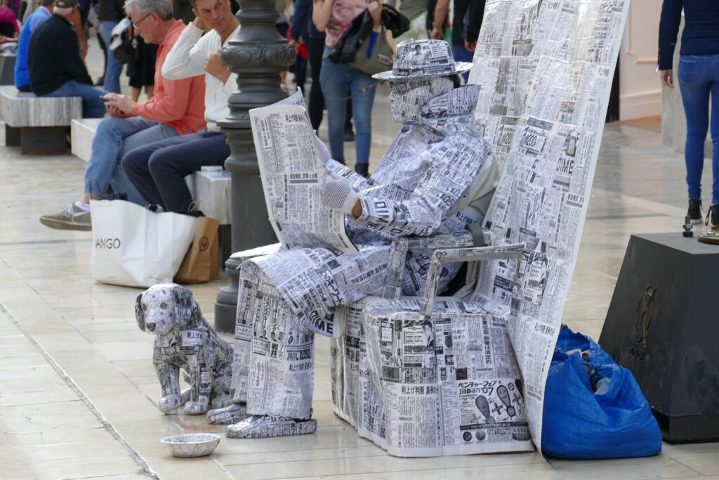 A man from Japan and his dog totally wrapped in newspapers. he is reading a newspaper and is sat on a pile of papers. Even his glasses are made out of print!