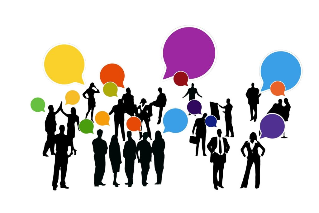 An illustration of a group of people who are gathered together talking in a group. They have multi-coloured speech bubbles coming from their mouths. This to demonstrate the use of groups in LinkedIn and how they can be helpful.