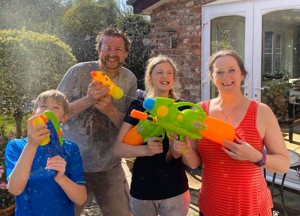 Picture of Becs with her family enjoying a water fight. Creating a waterpark feel in their back garden. This highlights the importance to include in your content strategy personal photos as well to prove you are a human being.
