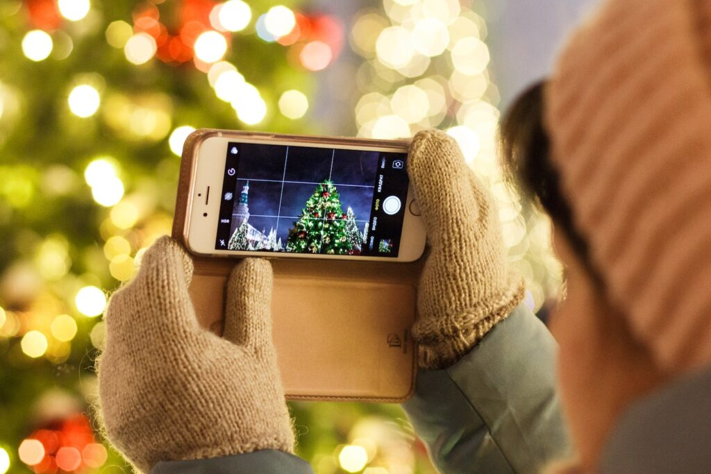 An image of a young girl holding a phone taking a picture of a Christmas tree. This is some of the great ideas for Christmas social media post.
