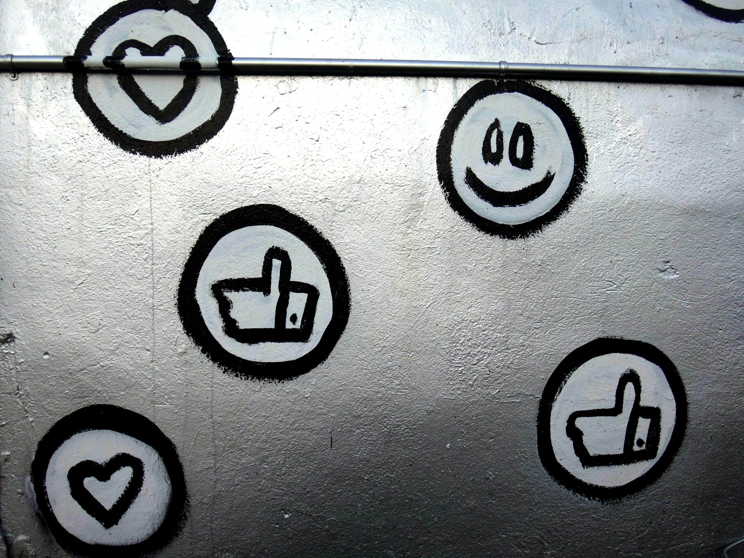 A sliver wall with black and white likes, smiles and heart graffiti. Showing that driving engagement is important and unique for each platform.