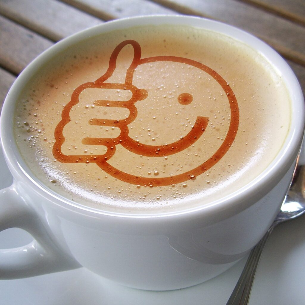 A delicious looking cup of coffee with a picture of a smiling thumbs up emoji. Showing when you want to sell through your social media you need to be friendly and approachable.