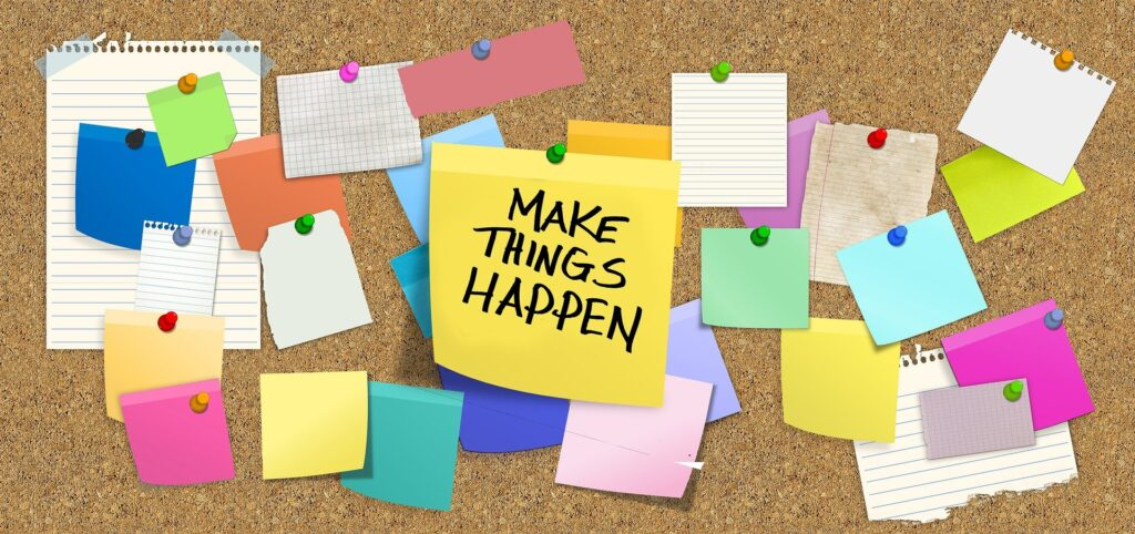 A cork board showing post it notes with one big one in the middle with 'Make Things Happen' hand written in black ink. Showing that a Social Media Plan is really important to success.